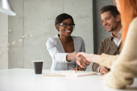 A female financial planner shaking hands with a client in Virginia